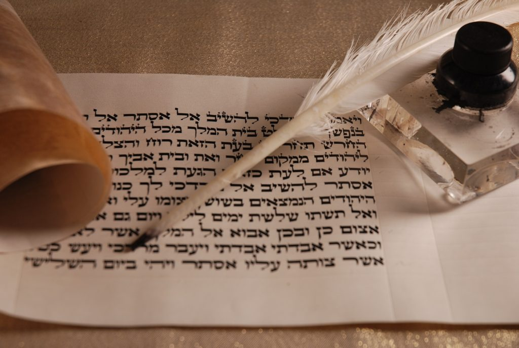 Hebrew letters on parchment with quill and ink well