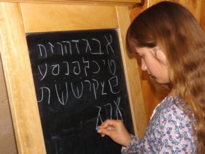 Girl writing aleph bet at chalkboard